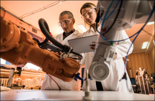 Technicians cooperating while working on robotic arm