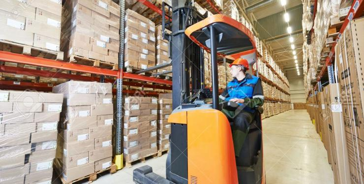 warehouse worker moves pallets with forklift